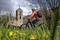 Woman on bike and romanesque church of Sant Feliu, Barruera, Vall de Boí, Lleida, Catalonia, Spain.