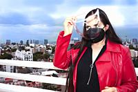 Caucasian woman using mask protection and putting plastic mask on her face to walk through Mexico City.