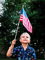 small boy holds a US flag over his head in a patriotic pose.