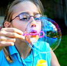 Girl blowing large soap bubbles from a bubble wand.