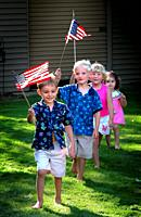 A parade of children marching holding flags over their head march in a line to celebrate thee 4th of July.