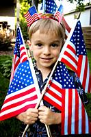 close up portratit of a little boy with the american flag flags pressed against his face.