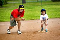 7 year old girl talking with her coach baseball lessons by being introduced to T Ball little league.