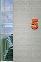 Orange house number 5 on the outer facade of a modern architecture with corner glazing.