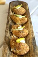 Meat croquettes on wooden tray.