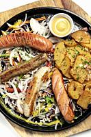 mixed german traditional organic sausage and potato meal platter including Nurenberger, Lamb and Pork with salad and mustard.