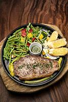 organic tenderloin beef steak sizzler on hot plate meal platter with mixed vegetables and chimichurri sauce.