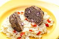 meat balls filled with red beans on rice with red pepper.