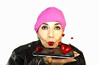 Mexican woman wearing pink kerchief and leather jacket, while hand holding a cell phone blowing kisses in the shape of hearts red balloons with a gest...