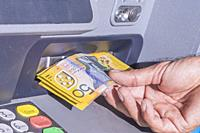 Taking several Australian $50 notes from an ATM machine.