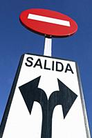 Traffic sign in Malaga, Spain. No entry disk and word Salida in Spanish, meaning exit, with arrows pointing in both left and right directions.