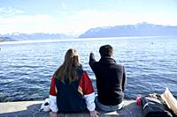 couple looking at mountains Cornettes de Bise, alps, behind lake Geneva, view from Lausanne, Switzerland, Europe.