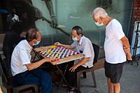 Singapore, Republic of Singapore, Asia - Elderly men wearing protective face masks play Chinese chess (Xiangqi) in Chinatown during the lasting corona...