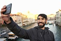 Turkish man taking selfie on bridge Ponte dell'Accademia at sunrise, morning in Venice, Italy, Europe.