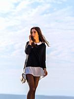 Teenage girl walking on seaside using her smartphone for talking.