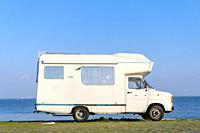Vintage camper van parked by the riverfront.
