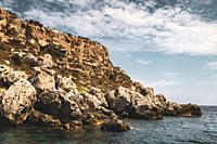 Rocky cliff face on south east coast of Menorca, Spain - Europe. This rugged coastline is a short boat ride from Mahon the capital of the island.