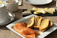 Slices of smoked salmon with toasted bread on square plate and cheese display for breakfast.