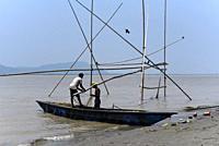 Fishermen lay fishing net in the in the Brahmaputra river, in Guwahati.