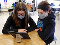 Students Wearing Masks and Sharing iPad in Special Education Classroom, Wellsville, New York, USA.