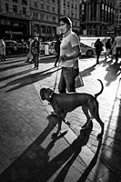 man with a dog in gran via street. Madrid. Spain.