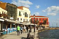 People in front of the Venetian style waterfront houses and traditional restaurants by the harbor in Chania city, Chania Province, Crete, Greek Island...