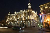 Old American cars and coco taxis in front of the Great Theatre-Gran Teatro and Hotel Inglaterra in Center Havana by night, La Habana, Cuba, West Indie...