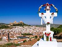 Cross adorned during the feast of the May Crosses, in the background, cityscape with La Mota fortress, of Islamic origin, on the hill with the same na...