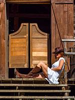 Mature woman in classic American West village environment is sitting on saloon porch