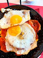 Fried eggs with ham and chips. Spain.