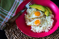 White rice with quail egg and avocado.