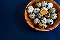 Quail eggs in a wooden dish.