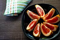 Grapefruit cut into pieces on a plate.