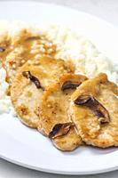 poultry meat with mushroom sauce and rice.