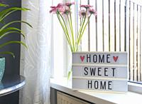 Sign Home sweet home text on lightbox ,windowsill near window with pink flowers, decorative frame modern interior background, stylish house cozy corne...