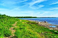 Colourful shea shore with clear blue sky. Tranquil summer landscape.