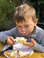 Boy 5 years old, eats waffle outdoors in Ystad, Sweden.
