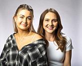 Two women, 25, in studio portrait, smiling.