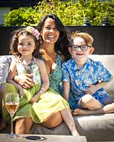 A mother and her two children celebrate a birthday on an outdoor patio, Vancouver, BC, Canada.