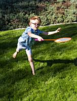 A 7 year old boy plays badminton on a lawn in Vancouver, BC, Canada.