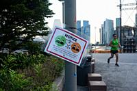 Singapore, of Singapore, Asia - A signpost in Marina Bay informs about the allowed group size of maximum 2 persons and the distance regulations for ou...