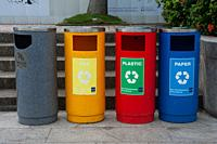 Singapore, Republic of Singapore, Asia - Colourful rubbish bins for waste separation with signs for recycling of reusable materials are seen at the wa...