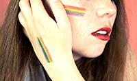 Portrait of a young woman with rainbow Flag on cheek and body, the LGBT community on a colorful pink background freedom, LGBTQ concept beauty.