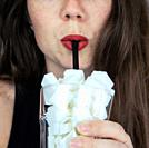 Portrait of young woman drinking with a black colored straw from a glass filled with sugar cubes Junk food, unhealthy diet, too much sugar on drinks, ...