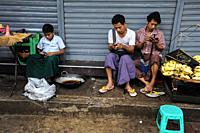 Yangon, Myanmar, Asia - Three young people stare at their mobile phones and spend their time playing games or browsing the internet.
