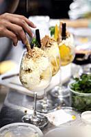 detail of staff making italian gelato ice cream sundae in modern shop.