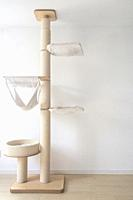 Cat scratching post wall mounted in modern room for pet on white wall, stylish decoration for cat owner with copy space.