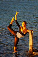 Ballerina performing in shallow water lit by warm evening sunset sidelight