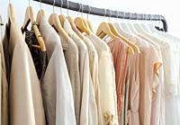 Stylish womans clothes hanging on a rack natural colors, trending concept,pastel colors in white room modern design closeup storage.