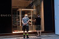 Vienna, Austria, Europe - Two men stand in front of a shop window of a Gucci fashion store in a pedestrian zone in the Austrian capital city.